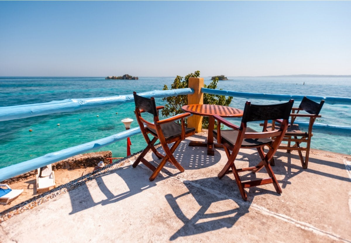 Terrace on the sea with wooden table and chairs