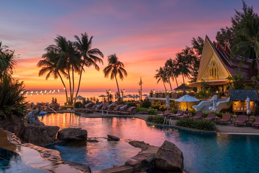 Koh Chang, Thailand - December 18, 2018: Beautiful sunset view with palm trees reflecting in swimming pool in luxury