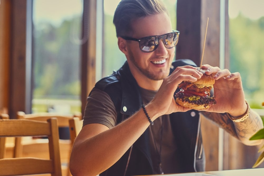 attractive man eating burger